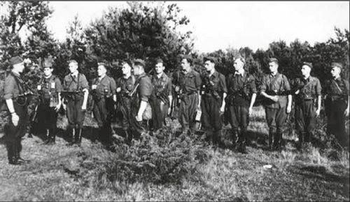"""Lato 1945, Podlasie. Obwodowy patrol żandarmerii AK podlegającym Komendzie Obwodu AK, następnie DSZ, Sokołów Podlaski; NN """"Szefunio"""" składa raport dowódcy Adamowi Tutakowi """"Zniczowi""""; od lewej stoją: Stanisław Tutak """"Cień"""", Kazimierz Wyrozębski """"Sokolik"""", Kazimierz Jarosiewicz """"Zimny"""", Stanisław Mróz """"Ciepły"""", Kazimierz Uszyński """"Szatan"""", NN """"Sęp"""", Roman Ratyński """"Rafał"""", Antoni Wojno """"Zbyszek"""", Roman Mizikowski """"Jurek"""", Kazimierz Zygmunt """"Flieger"""", Stanisław Jaroszewicz """"Stacho"""""""