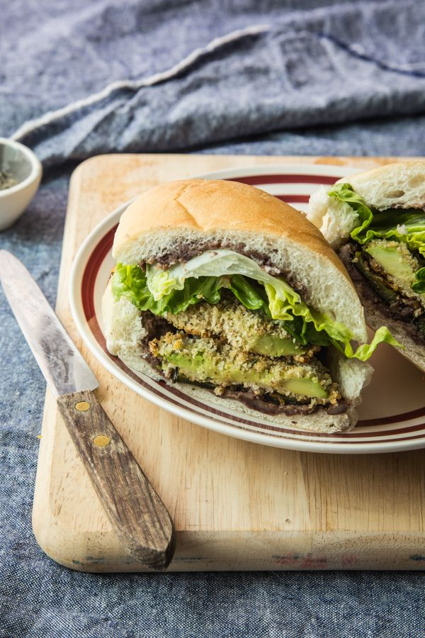 Crispy panko crusted avocado slices and roasted poblano peppers are stuffed into a crusty roll slathered with flavorful black bean spread in these vegan tortas.