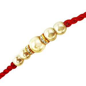 White Shell Pearl Rakhi: White shell pearl rakhi with red thread. Costs Rs 251/- http://www.tajonline.com/rakhi-gifts/product/r2167/white-shell-pearl-rakhi/?aff=pinterest2013/