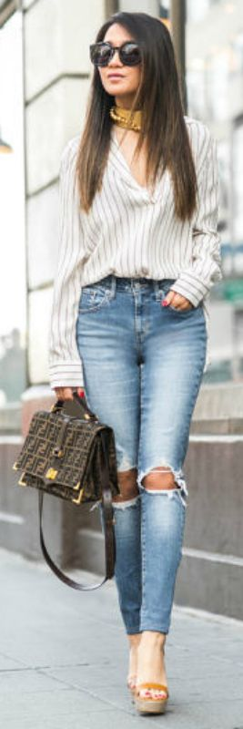 Wendy Nguyen + high-waisted form-fitting jeans + ripped, distressed and high waisted jean + causal yet comfortable + soft pin-striped shirt + platform sandals + Fendi bag + oversized sunglasses + chic street-wear look.  Shirt: Frame, Jeans: Levi's, Bag: Fendi, Shoes: M.Gemi, Sunglasses: Karen Walker, Watch: Daniel Wellington