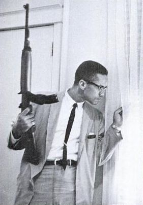 Malcom X holding a M1 Carbine and peering behind a curtain in response to death threats against him and his family 1964
