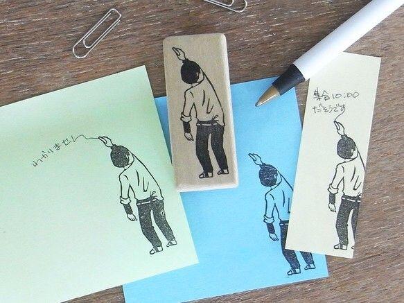 男子高生が黒板に何かを書いている挿絵はんこです。ちょっとした手紙や付箋、メモ等にどうぞ。女子高生ver.と絡ませても面白いかも…※1つ1つ手彫りの為、画像とは若干の違いが出る事ご了承下さいませ。印刷面はゴム板、取っ手は木、その間にコルクを挟んでいます。印刷面サイズ:約H4.7×W1.6㎝捺印するときはインクを付けすぎず印字面全体にパタパタと付け(インクを盛りすぎると潰れる事があります)、ギュッと押して下さい。印刷面は版画用ゴム板ですので固めです。紙質や押す力の加減等により印刷にムラができる可能性がございますが、それも味としてお楽しみいただけるかと思います