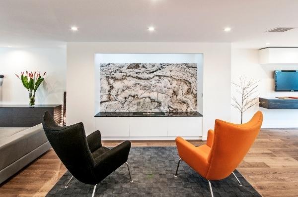 In the modern, open plan living room below, a beautiful piece of marble backs the gas flame fireplace. Like an artwork, the marble catches your eye as soon as you enter the generous space.