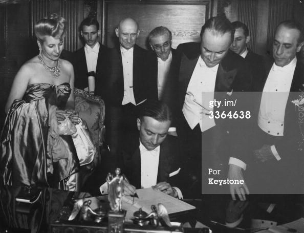 25th July 1947: French foreign affairs minister Georges Bidault signing a trade agreement between France and Argentina at a dinner at the Quai d'Orsay, Paris. Watching him is Eva Peron (1919 - 1952), wife of Argentine president Juan Peron. (Photo by Keystone/Getty Images)