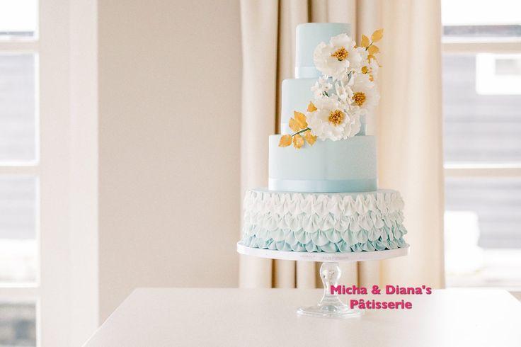 Blauwe bruidstaart met witte en gouden bloemen. Island paradise.