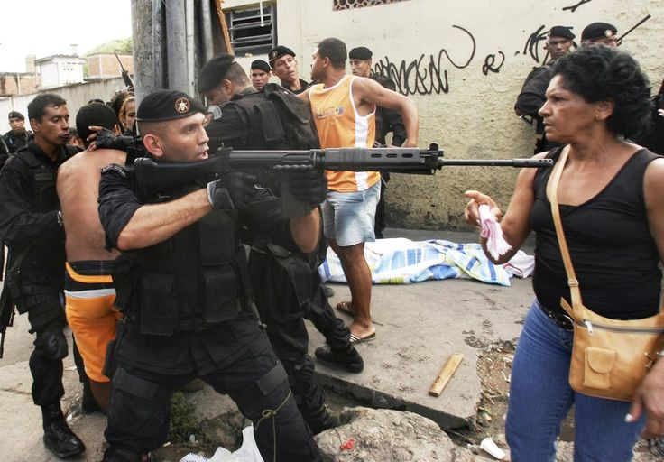 A police officer aims a machine gun at a woman as people protest beside a body killed during a shootout involving police and suspected drug traffickers at the Complexo de Alemao slum in Rio de Janeiro, Tuesday, Feb. 13, 2007. The violence comes just before the city's Carnival celebrations next Feb 18 and Feb 19. Rio is one of the most violent cities in the world with an annual homicide rate of about 50 per 100,000.