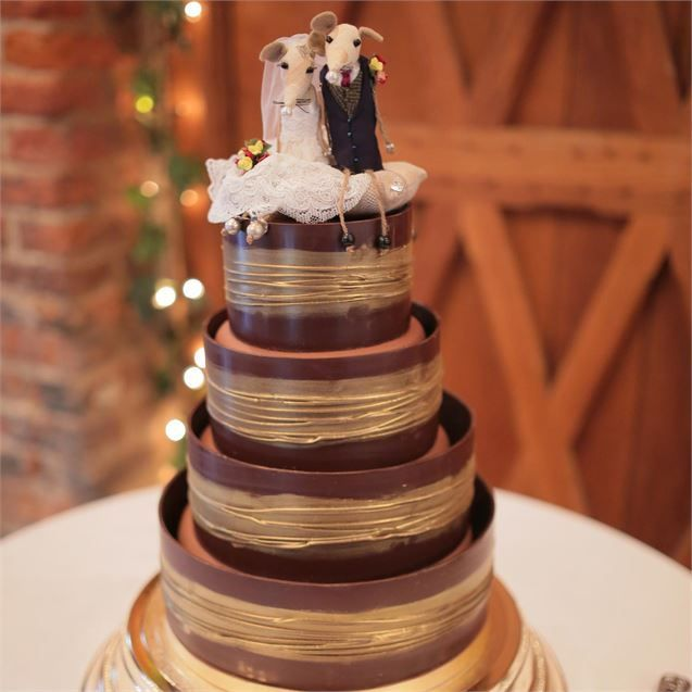 <p>In the evening, Dennis and Stephanie cut into a chocolate wedding cake decorated with shimmering gold hoops which they got from Marks and Spencer