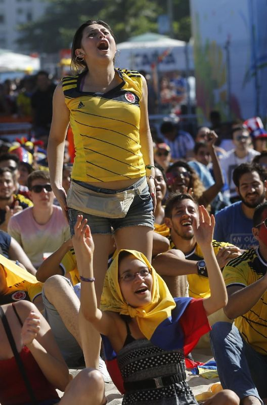 Colombia soccer fans cheer during their team's World Cup game against Greece inside the FIFA Fan Fest area on Copacabana beach in Rio de Jan...