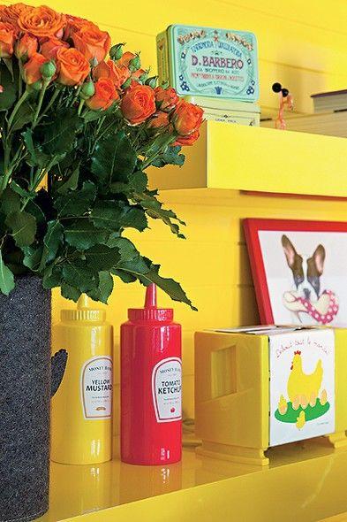 Tubos de ketchup e mostarda e latas antigas viraram objetos de decoração na estante amarela da arquiteta Letícia Arcangeli. O quadro com a imagem de um cachorro comendo sapatos também traz um toque de humor