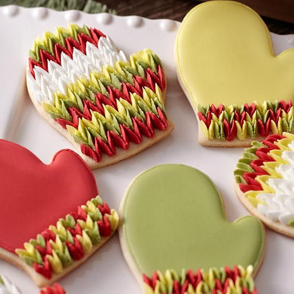 Knitted Mitten Cookies - Rows of petals piped in sweet pea fashion give these cookies the look of your favorite wool mittens. Use the Comfort Grip Mitten Cutter and Color Flow icing in warm winter colors to create these delightful treats.