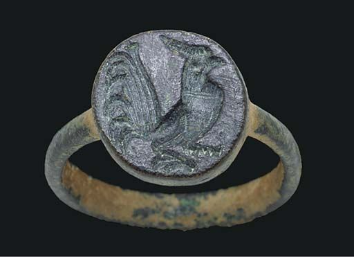 A LATE ROMAN OR BYZANTINE BRONZE FINGER RING  CIRCA 5TH-6TH CENTURY A.D.  Cast with a plain hoop, round in section, tapering slightly towards the shoulders, and merging with the underside of the disk-shaped bezel, engraved with a gamecock, raised up on his pointed toes, the comb swept back, the chest swelled, his tail fanning