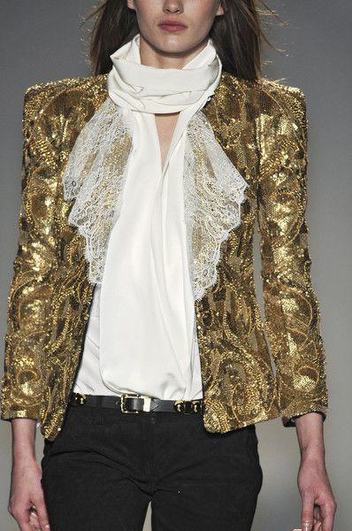 Balmain : Runway fashion. Gold bedazzle fabric blazer with lace lapel & a white silk scarf. Black slacks & white top.