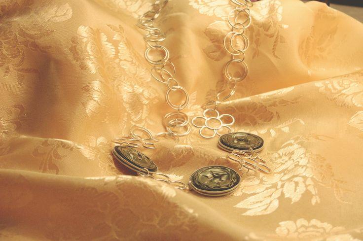 Paola – Verde oliva/militare con texture floreale nella cialda, catena corta a maglie floriformi e concentriche.