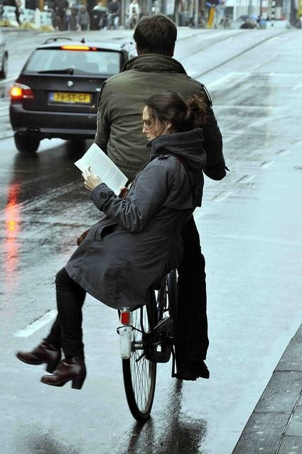 """""""Must be a good book,"""" Dec 2012 © Aude (Photographer amsterdamcyclechic via Flickr. Girl reading the book """"congo"""" on the back of a bike"""
