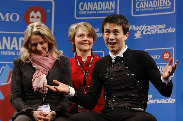 Choreographer Lori Nichol and Technical Specialist Christy Krall are sitting in the stands with Patrick Chan after winning gold at the 2010 BMO Canadian Figure Skating Championships in London, Ontario, Canada.