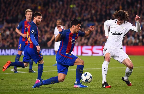 Paris Saint-Germain's midfielder Adrien Rabiot (R) vies with Barcelona's Uruguayan forward Luis Suarez (C) during the UEFA Champions League round of 16 second leg football match FC Barcelona vs Paris Saint-Germain FC at the Camp Nou stadium in Barcelona on March 8, 2017. / AFP PHOTO / Josep Lago