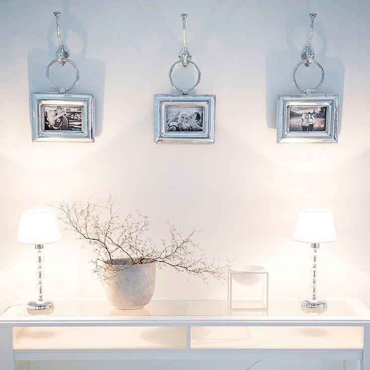 Rengasriipuksilla seinäkoukuista roikkuvat taulut, kauniit pöytävalaisimet ja minimalistinen kasvi luovat tunnelmallisen kokonaisuuden.