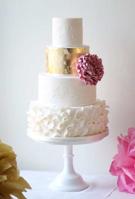 Brides.com: . A four-tiered wedding cake with gold-leaf and ruffle accents, from Ivory & Rose Cake Company.