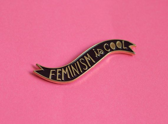Feminism is cooooool! This soft enamel lapel pin measures 1.75 inches wide. Black background and polished gold details, shiny and beautiful as