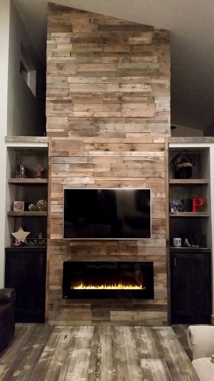 The reclaimed wood fireplace trend is only getting stronger. Pictured here in our All Natural Pallet Wood Prefab Panels.