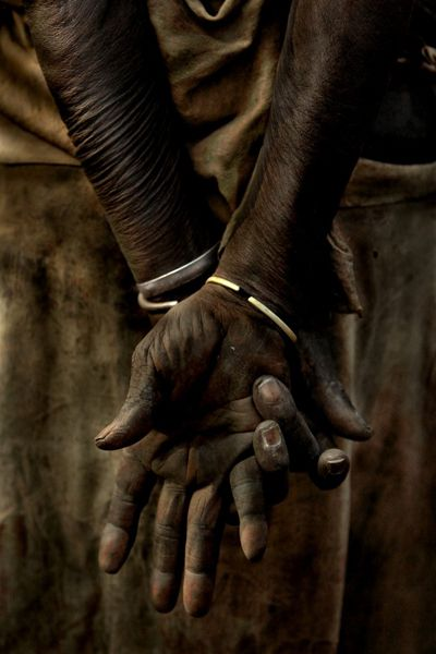 Mani consunte  Fotografia di Nicholas Wiesnet    Le donne Kara raccolgono l'acqua, cucinano per la famiglia, lavorano nei campi, confezionano i vestiti e sono la spina dorsale della tribù. Questa anziana era l'unica persona con i capelli bianchi con cui sono entrato in contatto. Ho tentato di farle un ritratto, ma ho pensato che le sue mani fossero il simbolo migliore del ruolo delle donne nella Valle dell'Omo. I bracciali sono fatti con bossoli di Kalashnikov recuperati, simbolo della faida…