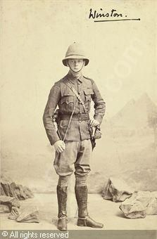A studio portrait of Winston Churchill in tropical uniform with pith helmet, spurs and sword before a backdrop depicting the pyramids - 1898