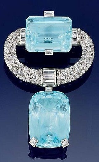 An Art Deco aquamarine and diamond brooch, circa 1930. The cushion-shaped aquamarine drop to a pavé old brilliant-cut 'c' scroll surmount with baguette diamond detail incorporating a single cut-cornered rectangular aquamarine. #ArtDeco #brooch