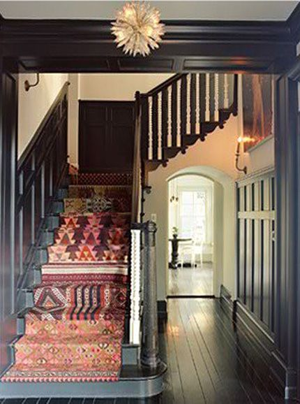 I'm not afraid of the dark! dark stained wood stairs, colorful eclectic stair runner, wood paneled walls.