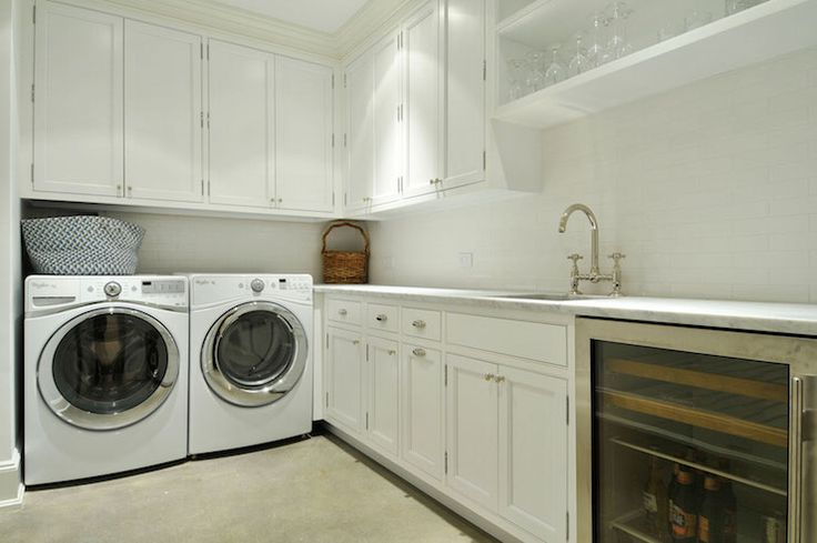 Laundry room and butler's pantry combo boasts white shaker cabinets paired with white marble countertops and a white linear tiled backsplash.