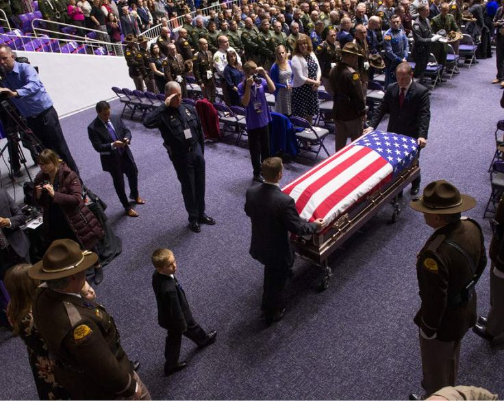 (Leah Hogsten     The Salt Lake Tribune)   l-r Utah Highway Patrol Lt. Lee Perry escorts Janica Ellsworth and her sons Ian and Bennett at the start of the funeral service for Utah Highway Patrol Trooper Eric Ellsworth Wednesday, November 30, 2016 at the Dee Event Center in Ogden on the campus of Weber State.  Ellsworth was hit by a car on the night of November 18, 2016while trying to alert the driver of a semitrailer truck to go around a downed power line in Box Elder County. He died four…