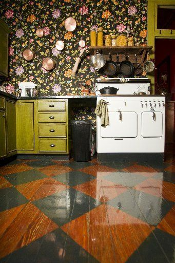 uk outlet stores In the kitchen  a diamond pattern is painted on the wood floor  the walls are upholstered with a floral fabric  and the cabinets are painted with a green  grain