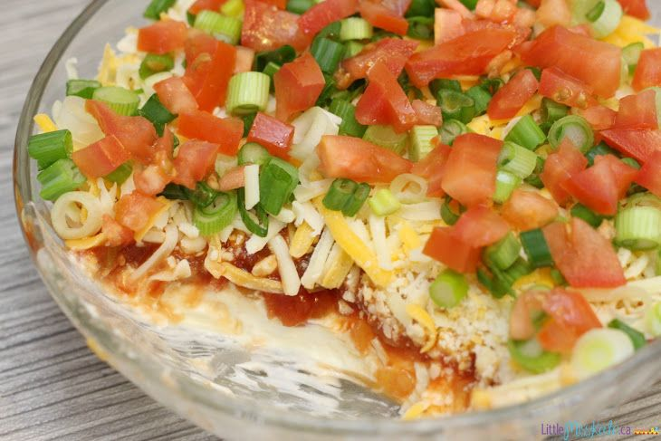 Easy Layered Nacho Dip Recipe Appetizers, Snacks with Philadelphia Cream Cheese, sour cream, Kraft Miracle Whip Dressing, salsa, crackers, tomatoes, green onions
