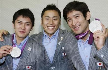 持ち帰った銀メダルを手に笑顔を見せるフェンシング男子団体の(左から)千田、太田、三宅=8日午後、成田空港(共同)