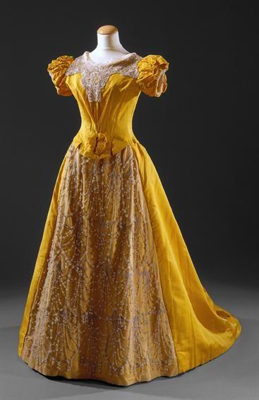 Vestido comprido, com corpete e manga curta em balão, com cauda tipico da segunda petade do século xix.