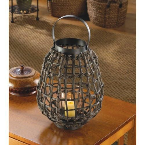 """Candleholders & Candles Home Locomotion This lantern is amazingly exotic and familiar, contemporary and vintage, and rustic and refined, all at the same time! The metal framework of this pear-shaped lantern is wrapped in chocolate brown rattan-like material, and inside is a simple, clear glass cup that awaits the candle of your choice. Set this stylish lantern on a table or mantel, or hang it from the top loop and enjoy the spectacular glow. Item weight: 1.6 lbs. 8"""" x 8"""" x 11&qu..."""