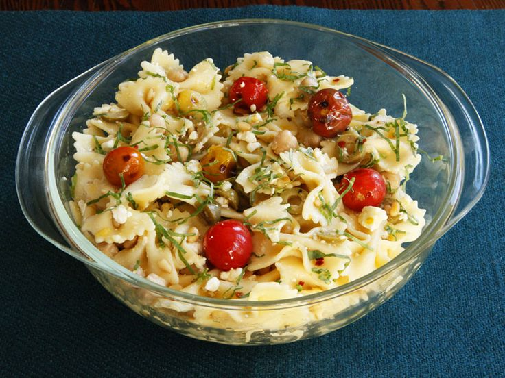 Recipe for a simple Mediterranean-style pasta salad with lemon, feta, chickpeas, roasted tomatoes, basil, olive oil and red pepper flakes for spice.