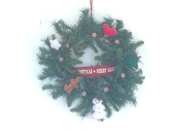 Christmas Wreath, the wreath itself is artificial, measures 16 inches in diameter, it has been decorated with cute little felt shapes, there is a Gingerbread Man, Snowman,Heart,Star,Tree. I have wrapped a red string ribbon that has little wood buttons on all around and then in the middle is a red hessian ribbon with Merry Christmas on. It hangs from red string.  As you can see from the photos I have decorated each shape by hand, all the decorations have been hand sewn on not glued. This…