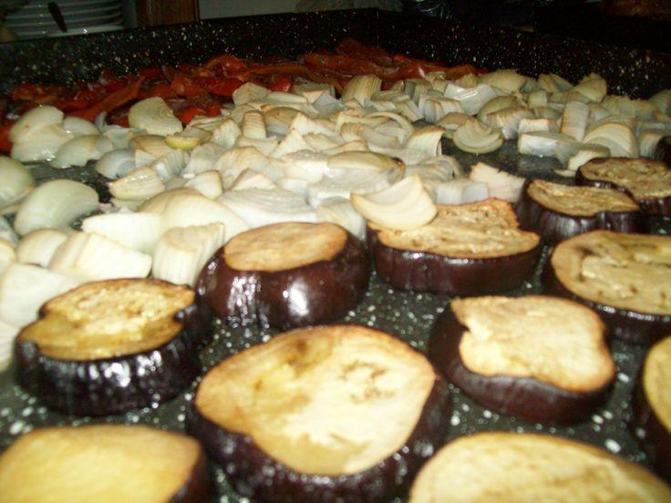 Variedad de verduras cocinadas en horno a leña: cebollas, pimientos, berenjenas con queso, papas
