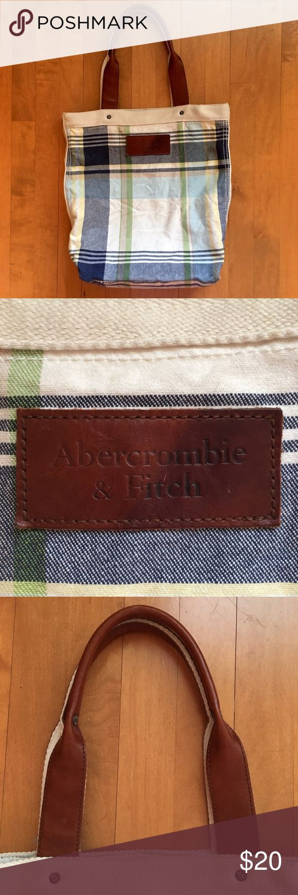 Abercrombie and Fitch Plaid Leather Tote Adorable plaid and leather tote by Abercrombie and Fitch in excellent used condition! It has a white cloth interior with a zipper pocket and a pouch.There are some light orange stains on the inside, mostly near the zipper pouch where an orange Gatorade spilled but not noticeable from the outside. Everything else is in great condition. Size: 14 x 14 inches. Abercrombie & Fitch Bags Totes