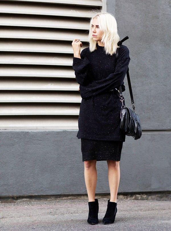 A black sweater and black skirt are paired with suede booties and a black leather tote.: