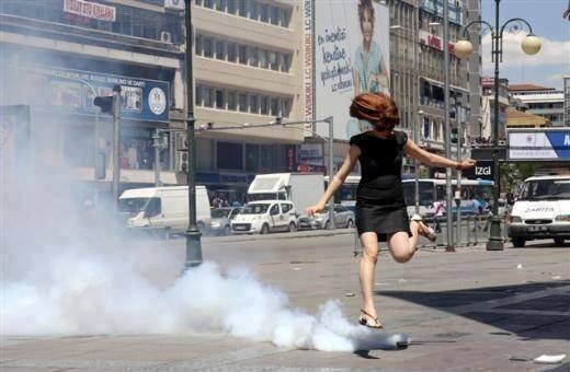 A young woman kicks back the tear gas.