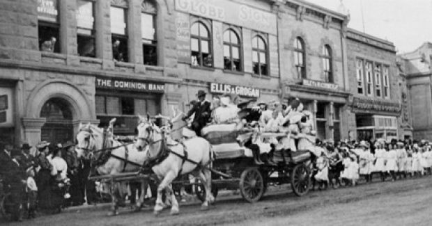 Pg 3 A Labour Day parade float passes the Dominion Bank in 1908, followed by little girls in white dresses. Beside that is Ellis & Grogan and Riley & McCormick's saddlery store in its first location, 111 Eighth Avenue. It later moved to 205 Eighth Avenue. (Glenbow Archives)
