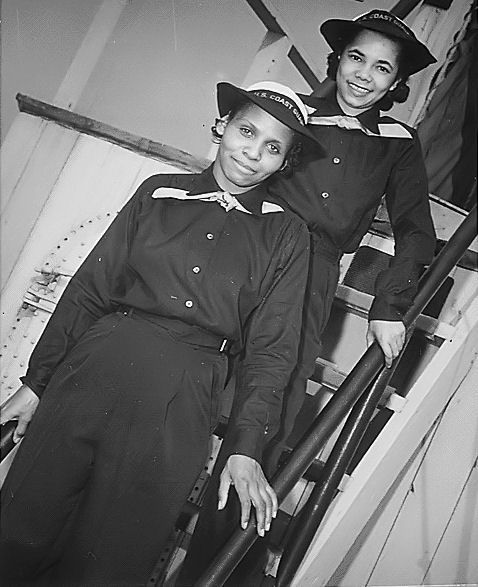 Two African-American SPARS pause on the ladder of the dry-land ship U.S.S. Neversail during their boot training at the U.S. Coast Guard Training Station, Manhattan Beach, Brooklyn, NY, during WWII ~