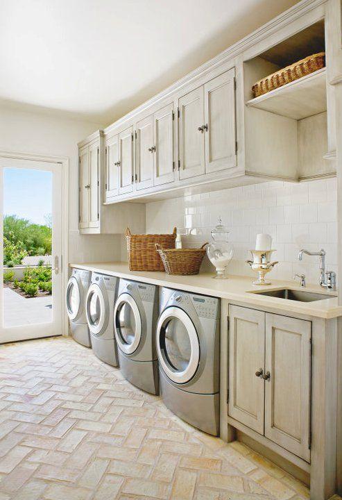 Amazing laundry room with herringbone brick floor, gray washed cabinets with cream countertops, laundry room sink, silver gray front-load washers & dryers and subway tile backsplash.
