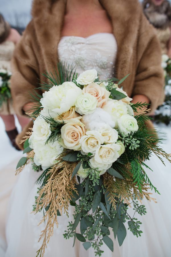 Winter bridal bouquet with white roses and evergreen sprigs. #WinterWedding #BridalBouquet #WeddingFlowers