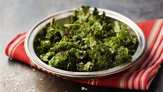 Värm ugnen till 150 grader. Repa bladen från den tjocka bladnerven. Lägg grönkålen på en plåt med bakplåtspapper och ringla över olivoljan. Vänd runt bladen så att det kommer olivolja överallt. Fördela bladen jämnt över plåten. Rosta grönkålen mitt i ugnen i 15-20 minuter så att de blir knapriga och krispiga. Salta före servering och njut som tilltugg eller som tillbehör på julbordet.