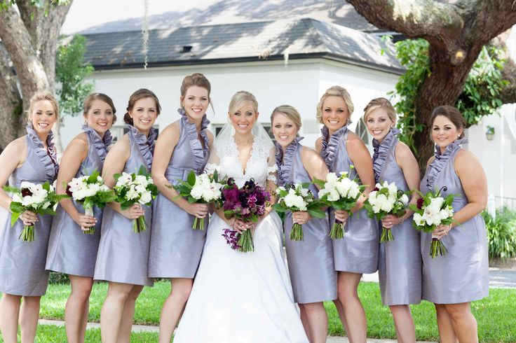 bride and her bridesmaids pose before heading into the chapel.  the bride carries a richly hued purple and lavender bouquet, her bridesmaids in lavender dresses carry all white bouquets, highlighted by a single burgundy dahlia.