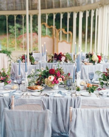 "Dinner Tables / Centerpieces held local anemones, vining peas, dahlias, hydrangeas, garden roses, clematis vines, and apple branches from the estate. ""I told the florist I wanted a really organic feel, with flowers spilling out of the vessels,"""