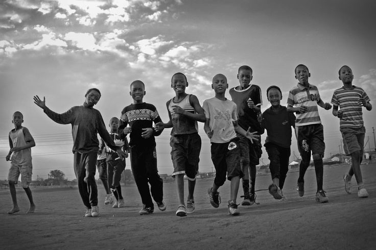 A photograph I took on a music video shoot in the Ikageng Township of Potchefstroom. The boys were warming up for football practice, on a dusty pitch at dusk.