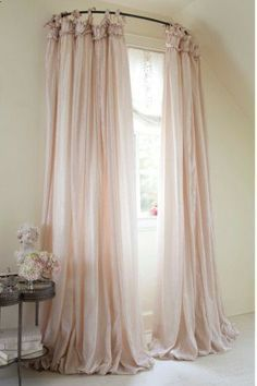 use a curved shower rod for window treatment… I really kind of like this. Its elegant and would be REALLY awesome in a princess themed bedroom with rich fabric.